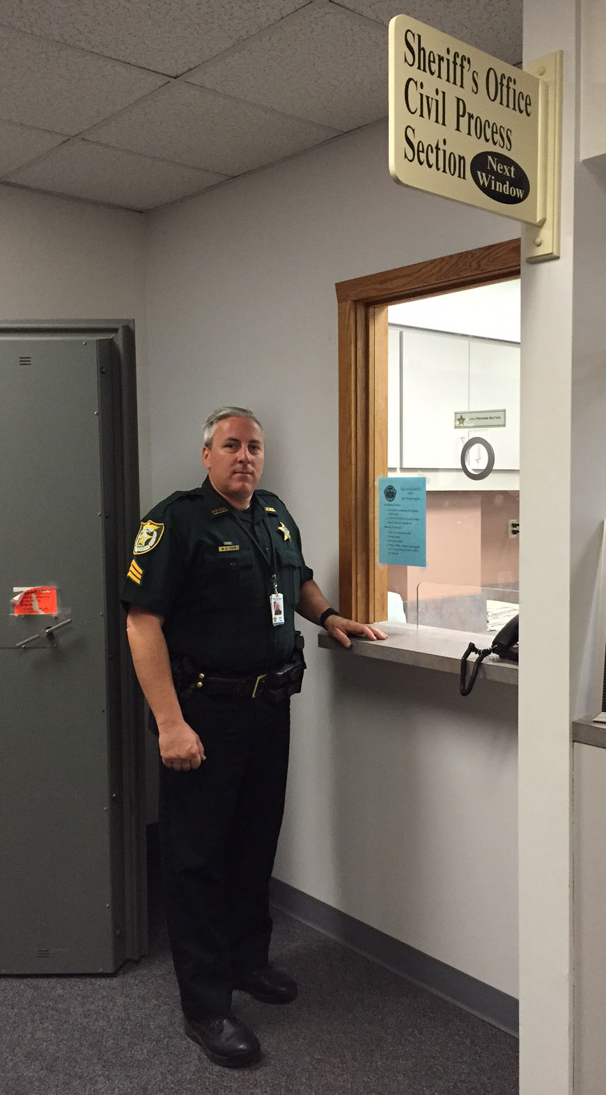 Mark Tate standing by the processing window of the Clay County Sheriff's Office Civil Section