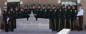 sheriffs taking photo next to memorial