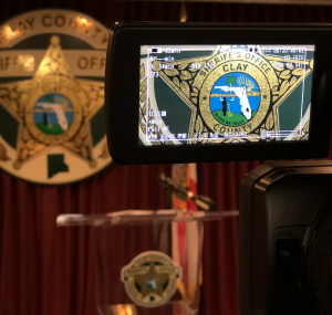 Camera with CCSO logo in viewfinder at a news conference