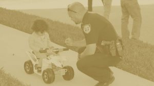 sheriff interacting with child riding toy four wheeler