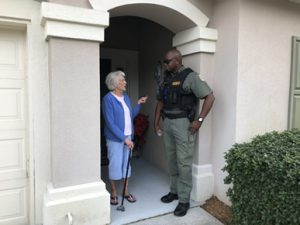 sheriff talking with woman in doorway