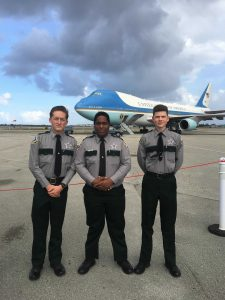 Youth camp members in front of plane
