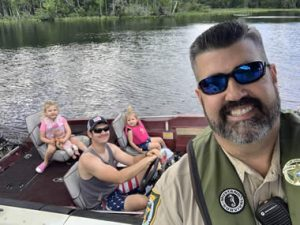 Sheriff taking picture with family on boat
