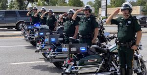 Deputies saluting next to their motocycles