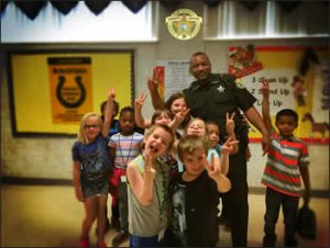 sheriff with school kids making peace signs