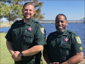 two sheriffs smiling in front of lake