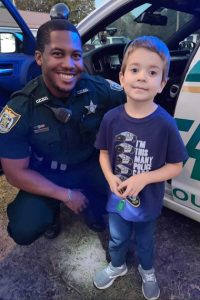 Sheriff and kid posing for picture in front of police car