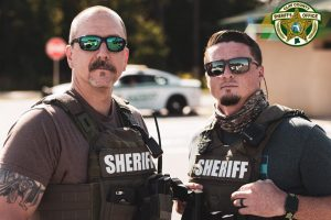 two deputies wearing their gear standing with sunglasses on