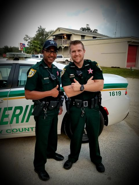 CCSO deputies smile and give a thumbs up to the camera