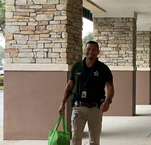 deputy walking outside a local shopping center