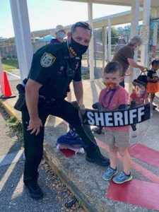 sheriff posing with kid holding shield