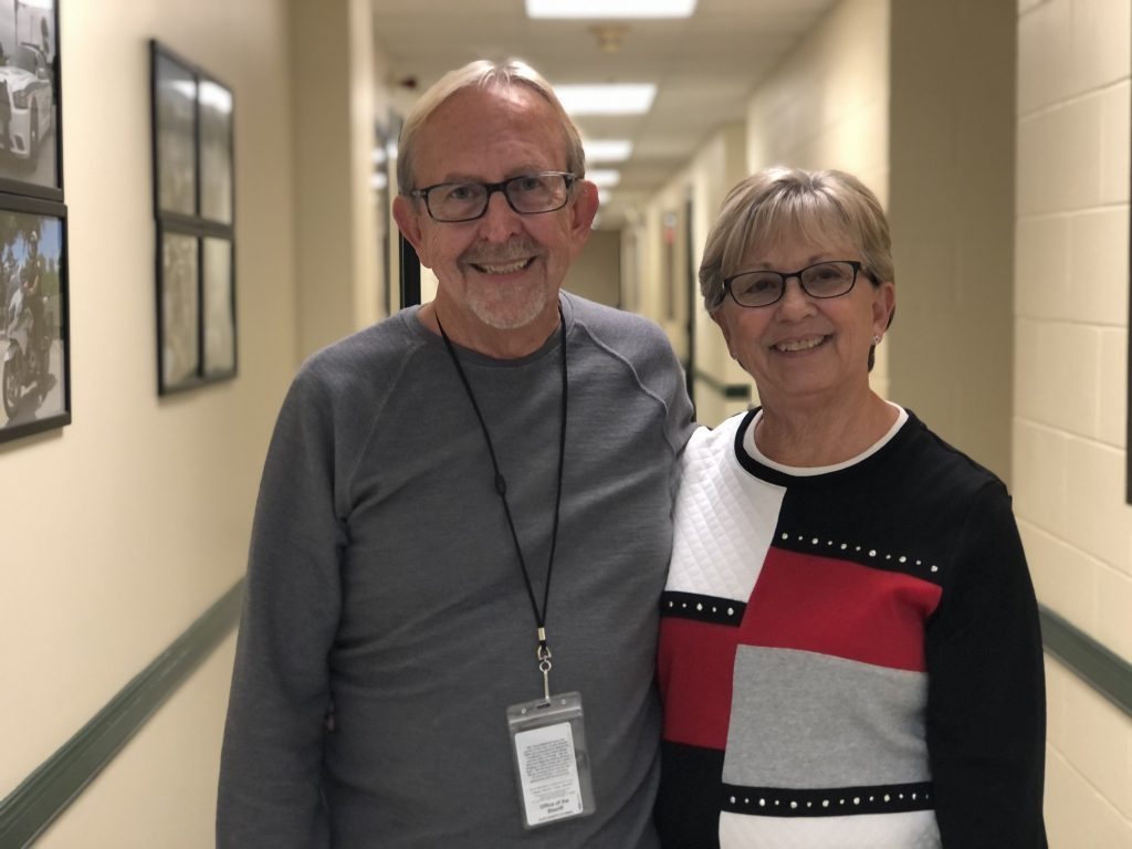 Picture of two people standing in a hallway smiling