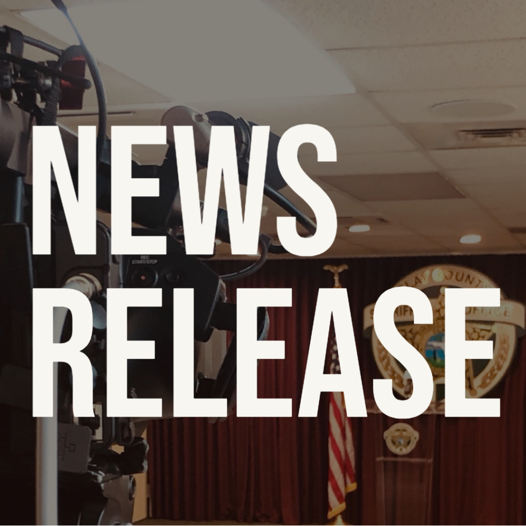 News release graphic, words against a darkened background with a camera looking at a podium