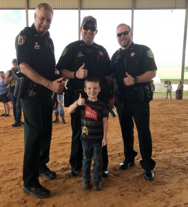 Patrol officers posing for picture with kid