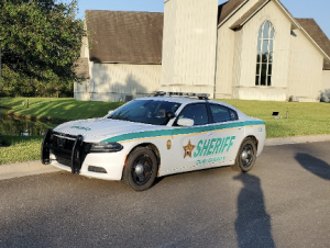 Deputy in a patrol car in front of a church