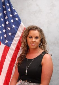 Portrait of Stacy Wase in front of a flag