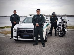 Deputies standing in front of a patrol car against the river