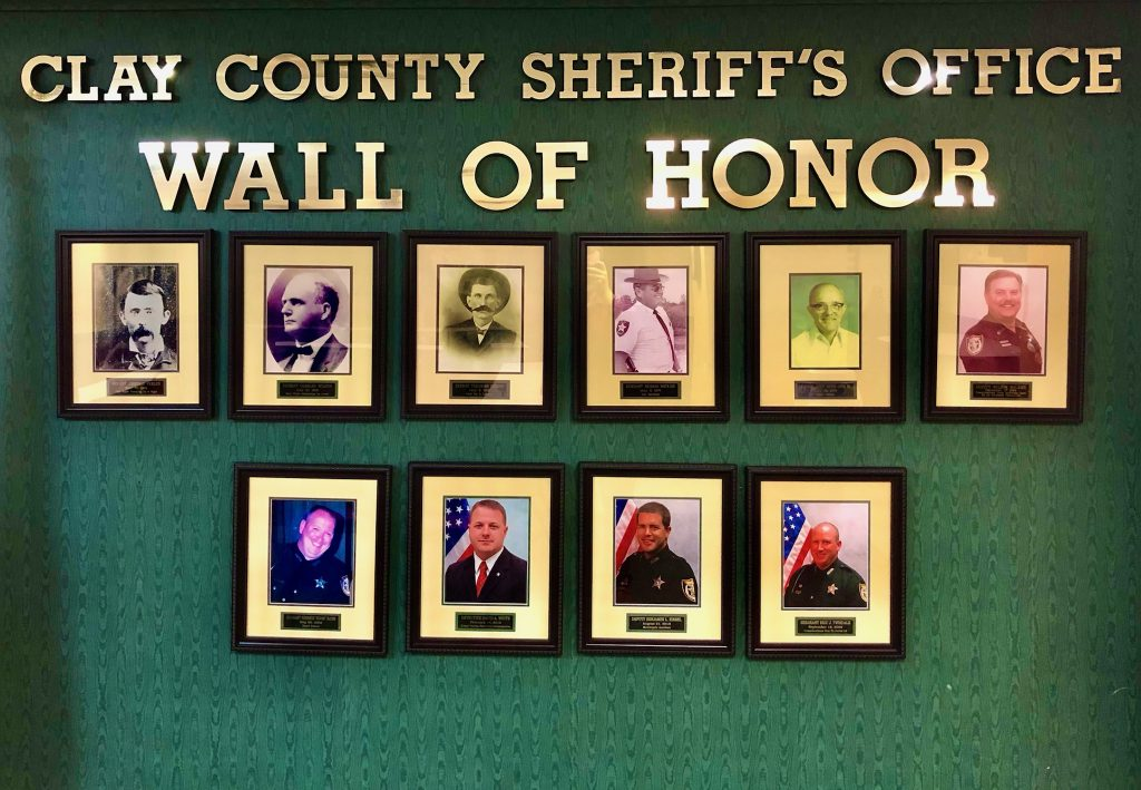 Picture of a wall of honor with photos of CCSO members who passed away in frames