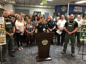 Sheriff Cook speaks at a podium with people behind her