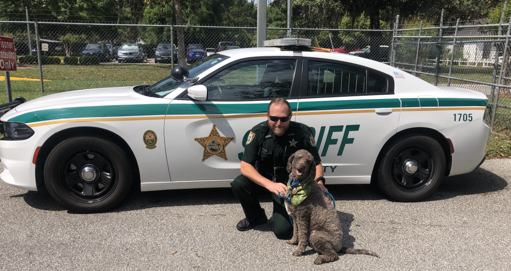 JP and a deputy in front of a patrol car