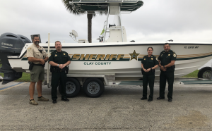 CCSO members standing in front of a Marine Unit boat